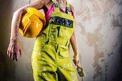 female in coverall holding paint brush and hardhat - stock photo