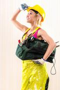 Stock Photo of female construction worker with tool bag indoors