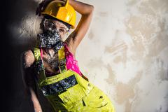 female construction worker wearing coverall, hardhat and respirator - stock photo