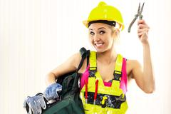 smiling female construction worker with tool bag posing indoors - stock photo