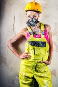 Stock Photo of female construction worker wearing respirator posing over obsolete wall