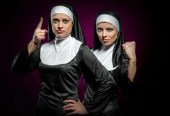 two attractive young nuns indoors - stock photo