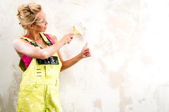 Female worker in coverall paint a  wall and showing thumbs up Stock Photos