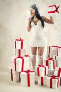 Stock Photo of woman as angel with heap of gift boxes shouting through megaphone
