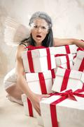Woman as angel with heap of gift boxes - stock photo