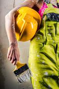 female in coverall holding paint brush and hardhat over white - stock photo
