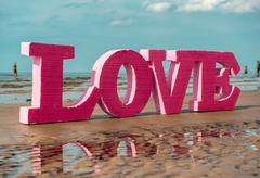 the word love on the beach - stock photo