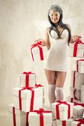 Woman as angel with heap of gift boxes posing indoors - stock photo