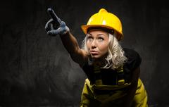 Stock Photo of attractive builder woman showing something with the hand, studio shot