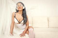 lovely angel girl in headphones listening music - stock photo