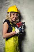 Attractive builder woman with a drill in her hands Stock Photos