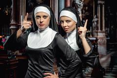 Attractive young nuns posing in the church Stock Photos