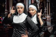 Stock Photo of attractive young nuns posing in the church