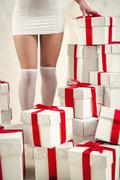 Woman's legs and heap of gift boxes Stock Photos