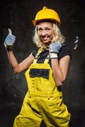attractive smiling builder woman with hammer showing thumbs up - stock photo