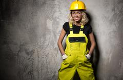 attractive builder woman posing against grunge wall - stock photo