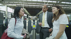 Young professional group chat as they walk through a London railway station Stock Footage