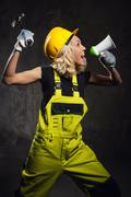 attractive builder woman shouting through megaphone - stock photo