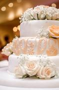Beautiful wedding cake decorated with orange roses Stock Photos
