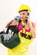 Female construction worker with tool bag talking by phone Stock Photos