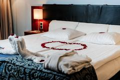 honeymoon bed decorated with red rose petals and towels - stock photo