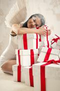 beautiful young woman as angel with heap of gift boxes posing indoors - stock photo