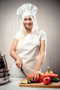 Woman wearing uniform cutting vegetables for a salad Stock Photos