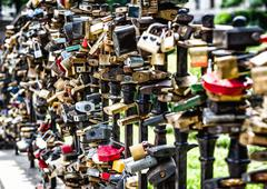 different shapes, sizes and colors of love padlocks affixed to a bridge - stock photo