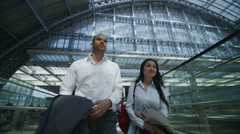 Young professional man & woman chat as they walk through London railway station Stock Footage