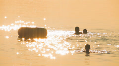 Children swimming on sunset Stock Footage