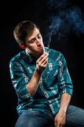 young man smoking cigarette - stock photo