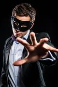 Elegant man wearing black mask posing indoors Stock Photos