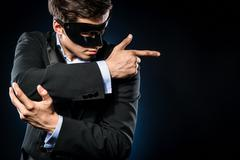 Elegant man wearing black mask posing indoors Stock Photos