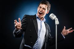 man in elegant black jacket and blue shirt singing - stock photo
