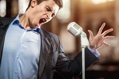 Man in elegant black jacket and blue shirt singing Stock Photos