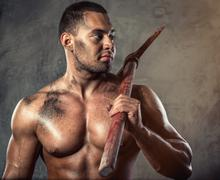 Muscular man holding pickaxe Stock Photos