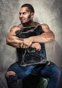 Muscular man with metal fuel can indoors Stock Photos