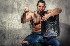 muscular man with metal fuel can indoors - stock photo