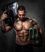 Muscular man with two metal fuel cans indoors Stock Photos