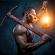 muscular man holding pickaxe and oil lamp - stock photo