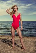 Attractive female in red swimsuit on the beach Stock Photos