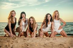 five beautiful and sexy ladies posing on the beach at sunset - stock photo
