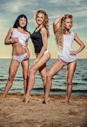 three sexy young women posing on the beach - stock photo