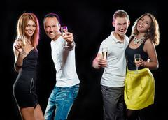 Cheerful group of young people with glasses of sparkling champagne Stock Photos