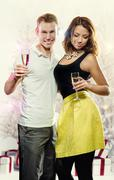 Young attractive couple with glasses of sparkling champagne Stock Photos