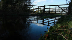 Country gates reflected in a puddle - dolly Stock Footage