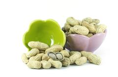 Dried peanuts in small cups on the white background Stock Photos