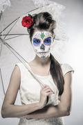day of the dead girl with sugar skull makeup holding lace umbrella - stock photo