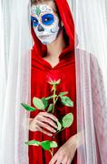 day of the dead girl with sugar skull makeup holding red rose - stock photo