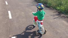 Kid with helmet riding bycicles with training wheels Stock Footage
